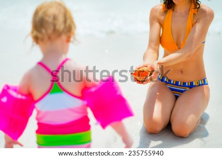 Closeup on mother showing shell for baby - stock photo