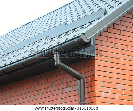 Closeup on new rain gutter system and roof protection from snow board (Snow guard)  on house construction - stock photo
