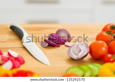 Closeup on onion and knife on cutting board - stock photo