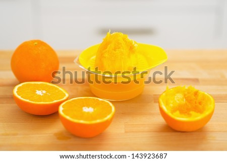 Closeup on oranges and juicer press on cutting board