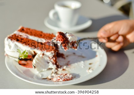 Closeup on person hand and delicious chocolate cake on sunny outdoors background - stock photo