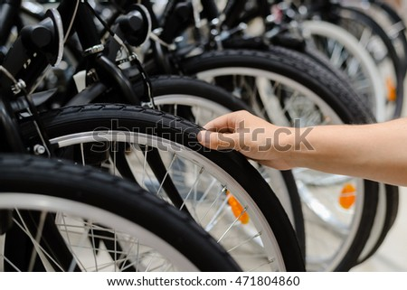 Closeup on person hand checking bicycle tire, shop factory background.