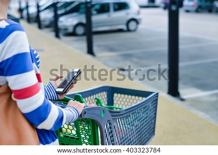Closeup on person holding mobile smart phone in hand during shopping. Cart on store parking background shopping - stock photo