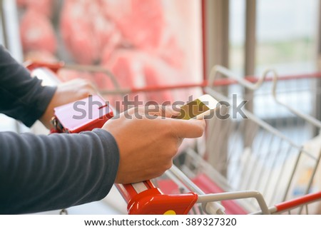 Closeup on person holding mobile smart phone in hand during shopping. Cellphone and cart on store goods background - stock photo