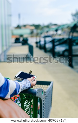 Closeup on person walking holding mobile smart phone in hand during shopping. Cart on store car park background. Back view  - stock photo