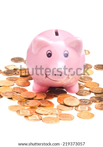 Closeup on pig-shaped pink money box and golden coins isolated over white background
