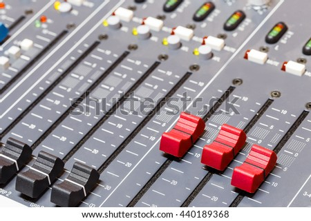 Closeup on red and yellow sliders of sound mixing console in audio recording studio