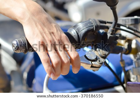 Closeup on rider's hand on the handlebar on sunny background