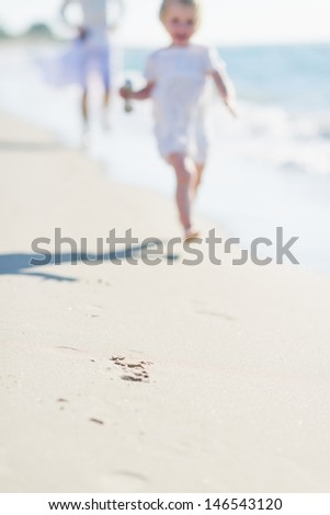 Closeup on sand and mother and baby running along sea shore - stock photo