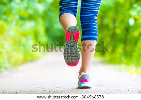 Closeup on shoe of athlete runner woman feet running on road  - stock photo