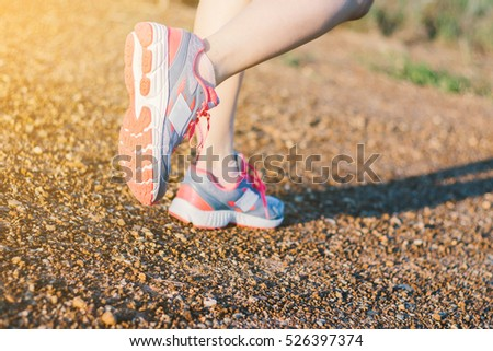 Closeup on shoes young lady running on the way ., at time sunset.