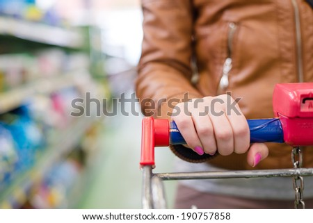 closeup on shopper woman hands on supermarket trolley carries with shopping mall display shelf on the background - stock photo