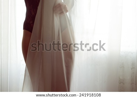 closeup on silhouette of hiding behind tulle curtain pretty lady with perfect fit body in black combies dress standing on light window copy space background