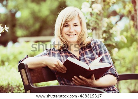 closeup on smiling blond mature woman reading book in park on sunny day