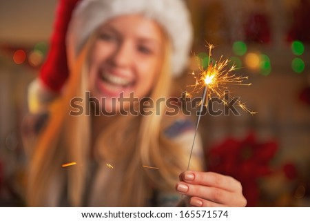 Closeup on smiling teenage girl in santa hat holding sparklers