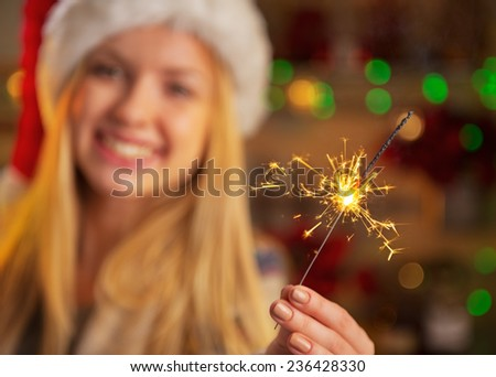 Closeup on smiling teenager girl in santa hat holding sparklers