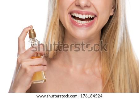 Closeup on smiling young woman applying perfume - stock photo