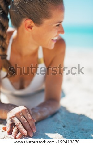 Closeup on smiling young woman in swimsuit laying on beach - stock photo