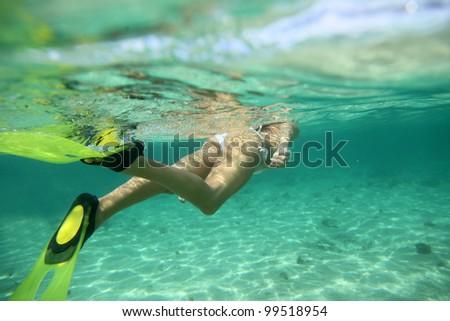 Closeup on snorkeler flippers underwater - stock photo