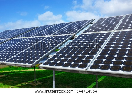 Closeup on solar panels capturing the sunlight over a blue sky - stock photo