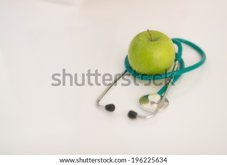Closeup on stethoscope and apple on table
