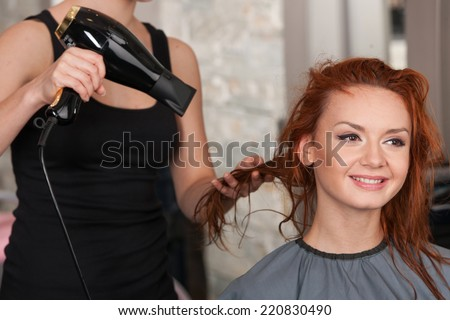 closeup on stylist hands drying redhead woman hair in salon. Young female giving new hair style to woman at parlor - stock photo