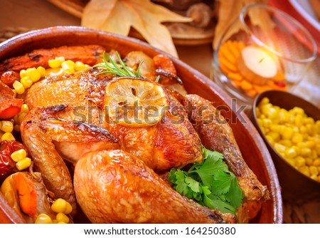 Closeup on tasty roasted chicken with vegetables on the table, traditional food of Thanksgiving day, autumnal holiday concept - stock photo