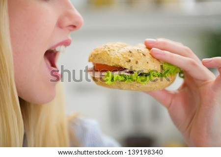 Closeup on teenager girl eating burger - stock photo
