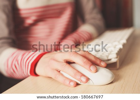 Closeup on the hand of a young woman as she is using a computer mouse