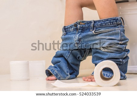 Closeup on the legs of a woman sitting on the toilet with jeans around ankles in morning and roll of toilet paper.