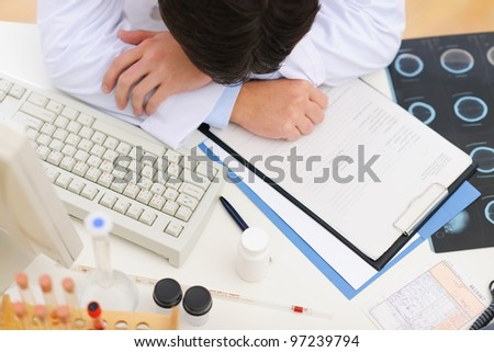 Closeup on tired medical doctor sleeping on table - stock photo