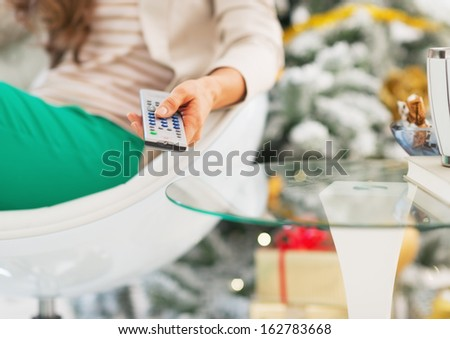 Closeup on tv remote control in hand of woman sitting near christmas tree - stock photo
