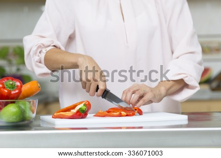 Closeup on woman cutting fresh vegetables in kitchen