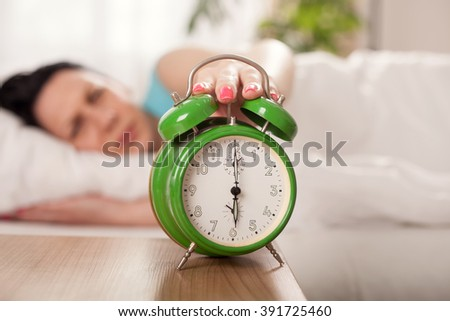 Closeup on woman hand reaching to turn off alarm clock