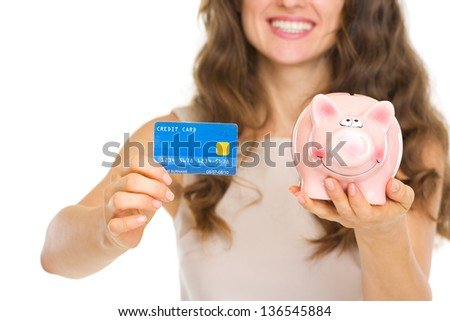 Closeup on woman holding credit card and piggy bank - stock photo