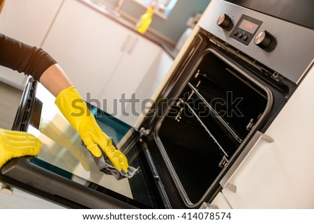 Closeup on woman's hands in yellow protective rubber gloves cleaning oven with rag - stock photo