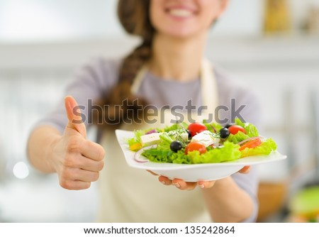 Closeup on woman showing fresh salad and thumbs up - stock photo