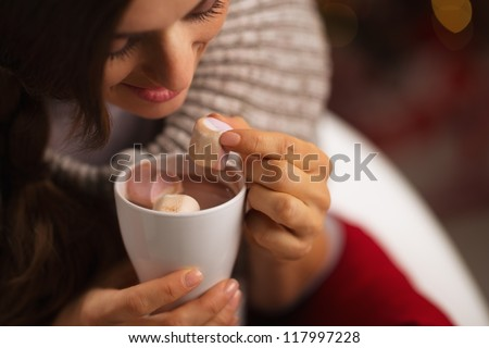 Closeup on woman taking out marshmallow from cup of hot chocolate - stock photo