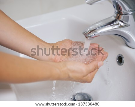Closeup on woman washing hands in sink