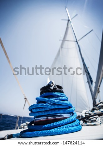 Closeup on yacht cord crank, rope holder on white sail background, yachting sport, sailboat detail, luxury water transport, summer vacation concept - stock photo