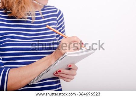 Closeup on young business woman taking notes on a meeting over white background