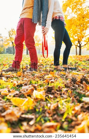 Closeup on young couple holding leash together in autumn park - stock photo