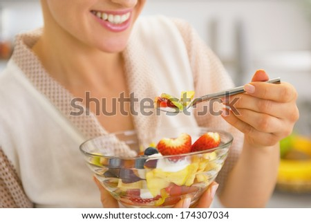 Closeup on young housewife eating fresh fruit salad - stock photo