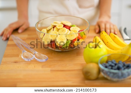 Closeup on young housewife making fresh fruit salad