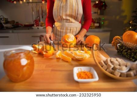 Closeup on young housewife making orange jam - stock photo