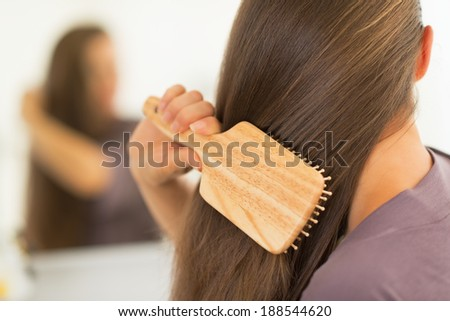 Closeup on young woman combing hair - stock photo