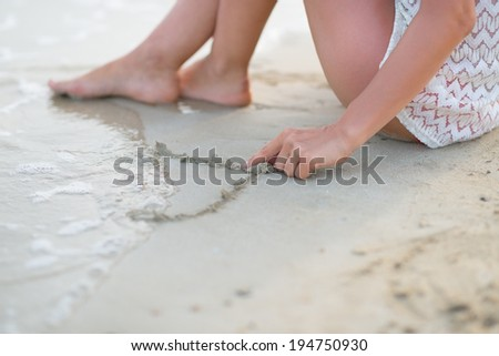Closeup on young woman drawing on sand