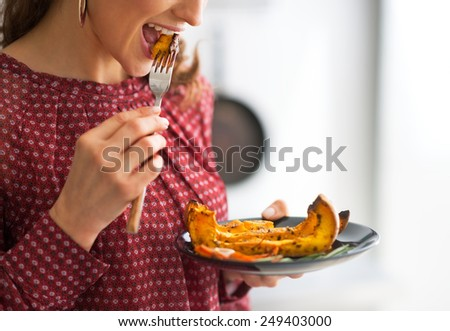 Closeup on young woman eating baked pumpkin in kitchen - stock photo