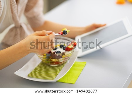 Closeup on young woman eating fruits salad and using tablet pc