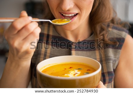Closeup on young woman eating pumpkin soup in kitchen - stock photo